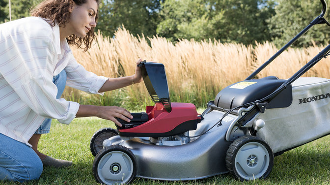 Side facing view of model demonstrating battery in lawnmower in garden location.